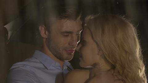 Handsome man looking passionately at blond woman, caressing gently, rainy night Footage