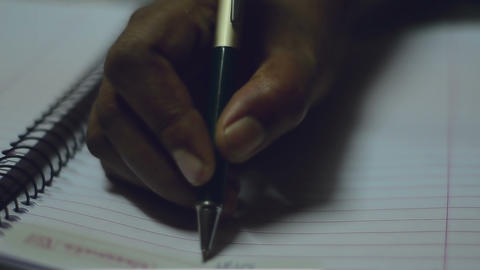 Close shot of writing using ball head pen over a spiral copy notebook GIF