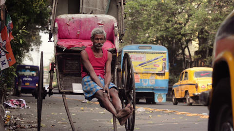 Medium shot of an Indian rickshaw puller waiting for the customer Footage