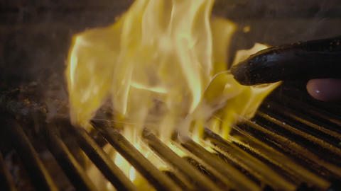 Steak slipping on the grill with fire slow mo Footage
