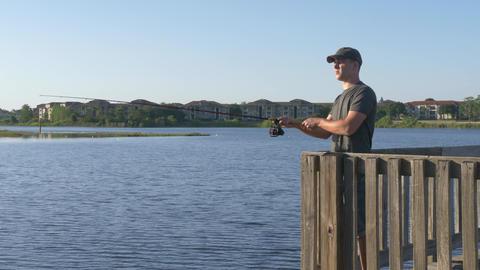 Fisherman cast fishing rod in lake or river water ビデオ