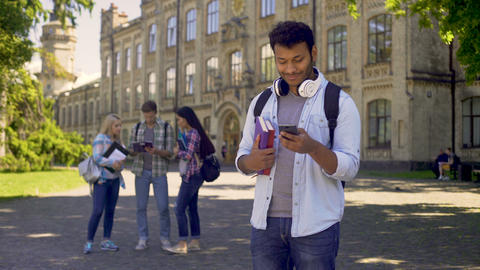 Cheerful male student using mobile app on smartphone, searching job online Footage