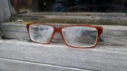 glasses at the right of the window of a wooden house in the top window Photo