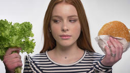 Young sweet ginger girl is choosing between healthy and unhealthy food, choose Footage