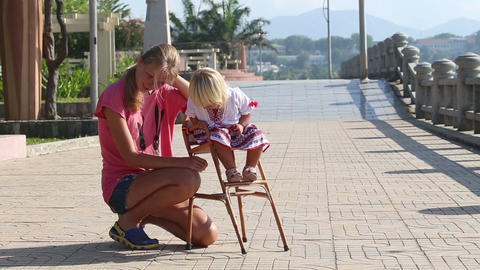 blonde girl in Ukrainian blouse sits on child's chair outdoor Footage