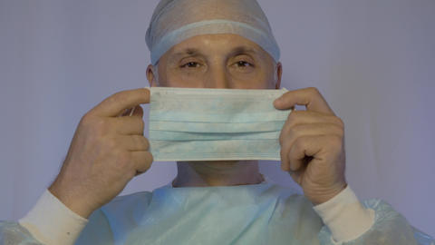 A white doctor surgeon puts on a medical mask before surgery. He is positively Footage