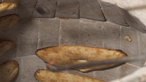 Cook take bread shoti with metal sticks from a wall Footage