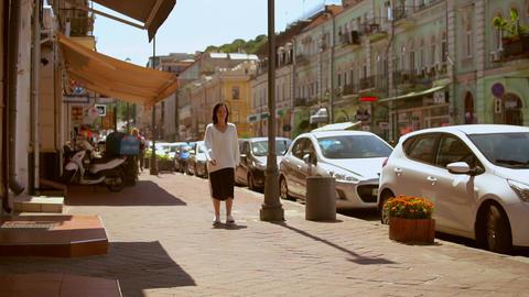 front view of a woman walking along beautiful street GIF