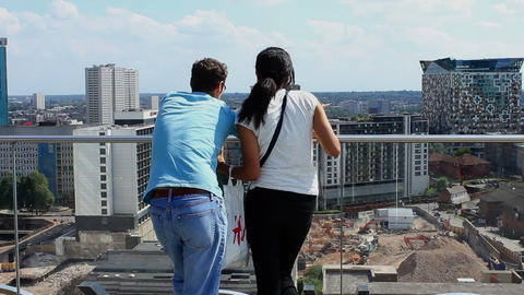 Pair of tourists viewing the overlooking cityscape from the terrace/skyline Footage