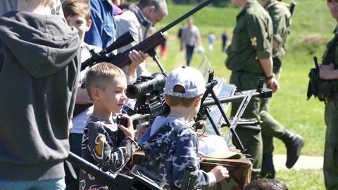 A boy shoots a gun at an exhibition Live Action