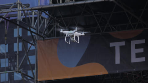 Modern Drone quadcopter with camera flying and shoots a concert on stage 영상물
