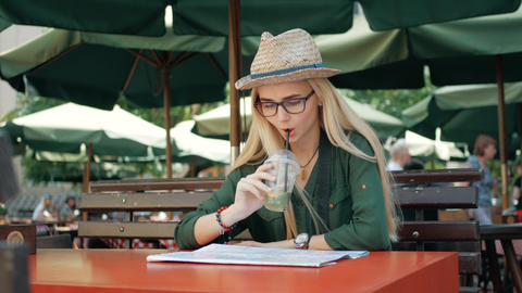 Young tourist woman exploring city map of lviv in cafe and drink while traveling ビデオ