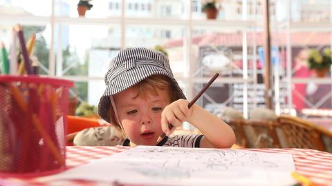 Kid draws on a piece of paper. Preschool education Footage