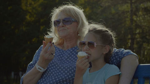 Kid eating eating icecream with grandmother outdoor Footage