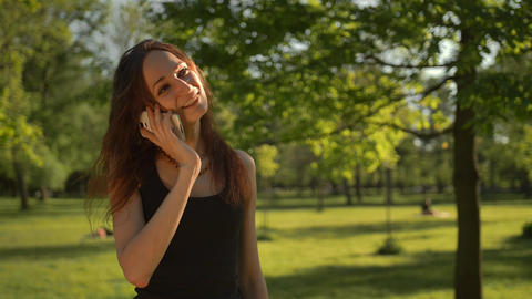 Smiling young woman stand at the park outdoors talk by phone Live Action