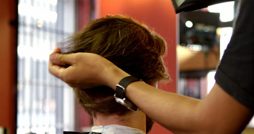 Man using hair dryer on customer hair 4k Footage