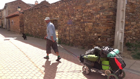 Pilgrim pull a cart with luggage after he greets other travelers who made a halt Footage