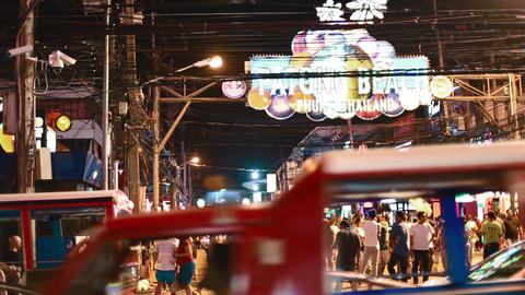 red trucks drive by big patong beach sign Live影片