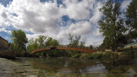 Clouds Moving Over A Bridge Cross A River Ciclyst And People Taking A Walk stock footage