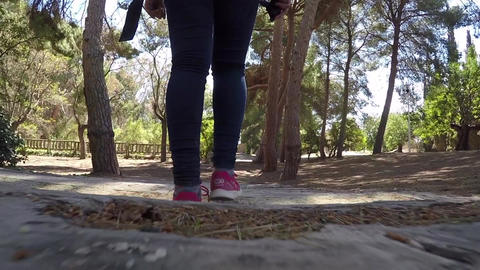 Girl walking through a natural park down stairs Footage
