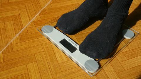 Man Weighing Himself With Bathroom Scales Footage