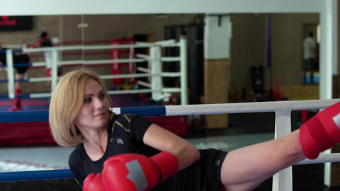 Beautiful woman in boxing gloves training her hits with coach at boxing ring Footage