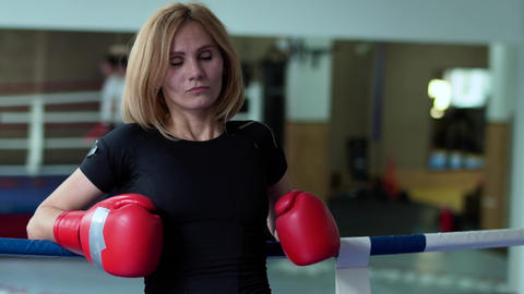 Woman in boxing gloves leans at ropes of boxing ring Live Action