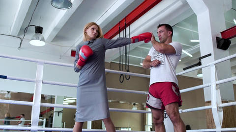 Pretty woman in dress and boxing gloves training with coach at boxing ring Footage