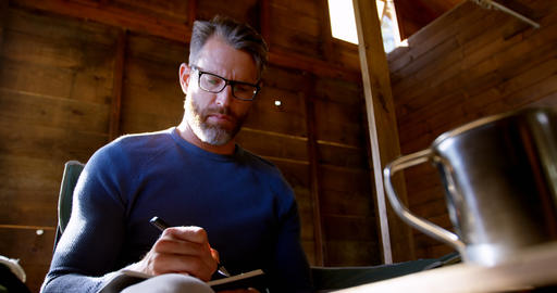 Man writing on a diary at home 4k Footage