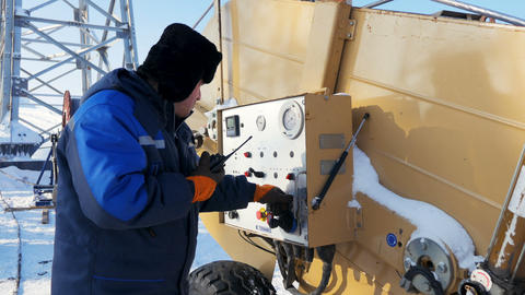 employee at dashboard speaks over portable radio by voltage tower in winter Footage