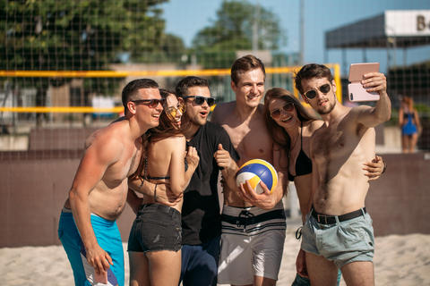 Group of smiling european friends making selfie on beach court フォト