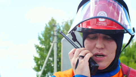 man in helmet with glass shield speaks over portable radio at competition Footage