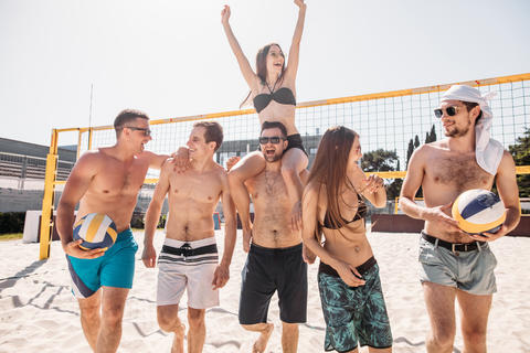 Group of young happy friends walking on beach volleyball court after game won フォト