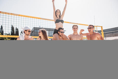 Group of young happy friends walking on beach volleyball court after game won Photo