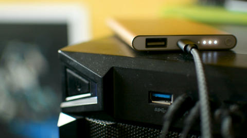 Mobile phone smartphone power bank connected and charging from PC in the dark Footage