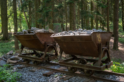 Mining cart with stones. Old and abandoned mining cart in forest Photo