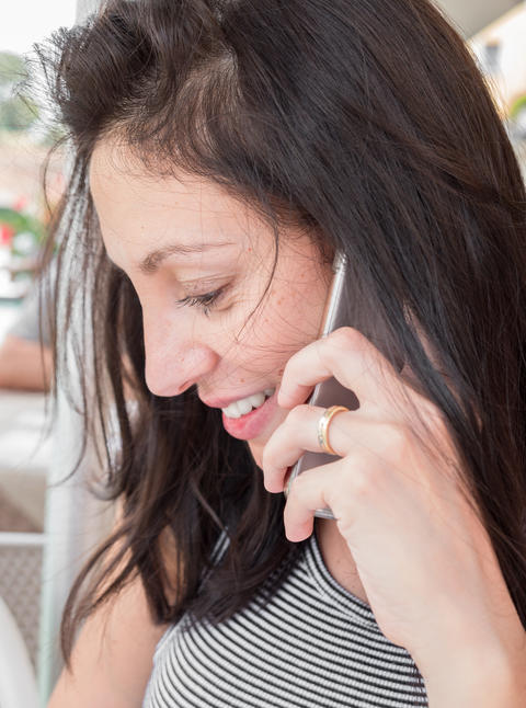 Brunette girl with a striped t-shirt talk on the cell phone Photo