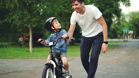 Slow motion of loving dad teaching his adorable son to ride bicycle in park ビデオ