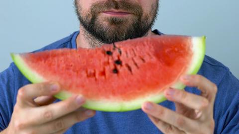 Bearded man eats a juicy watermelon, time-laps Footage