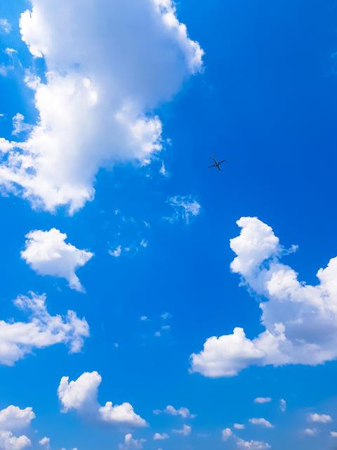 Plane Flies through the Clouds フォト