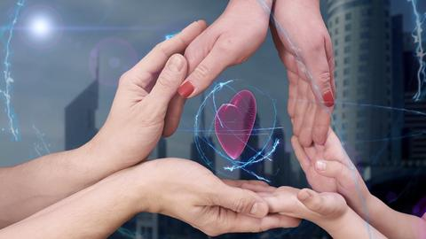 Men's, women's and children's hands show a hologram 3D heart フォト