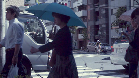 People cross the street in a business district of Tokyo, Japan in slow motion Footage