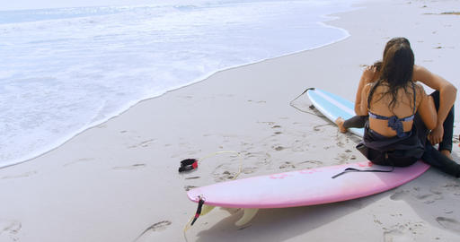 Surfer couple romancing on the beach 4K 4k Footage