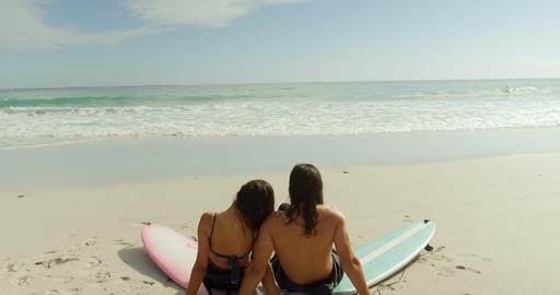 Surfer couple sitting on the beach with surfboards 4K 4k Live Action