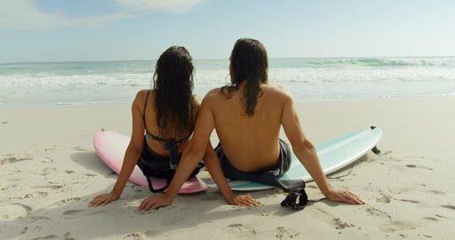 Surfer couple sitting on the beach with surfboards 4K 4k Footage