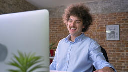 Happy businessman with curly large hair cheering about victory, winner sitting Footage