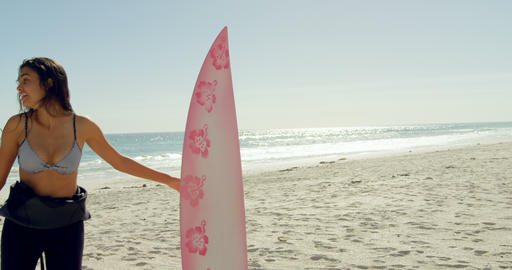 female surfer playing around the surfboard on beach 4K 4k Footage