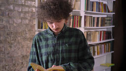 Smart nerdy student with curly hair reading book in library and standing Archivo