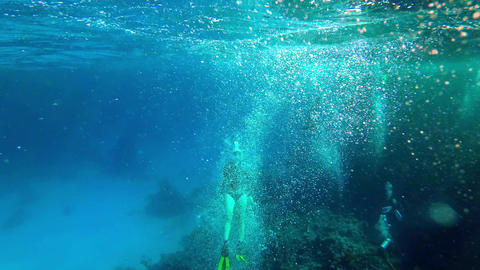 A female freediver ascending from the ground in a wall of bubbles next to a Live Action