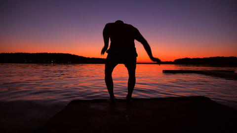 Man Jumping Into the Water from Wooden Pier During Amazing Sunset. Super Slow ビデオ